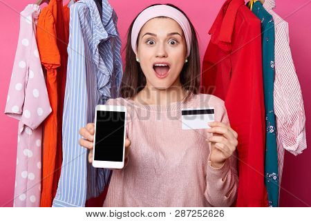 Portrait Of Excited Young Dark Haired Girl Shows Plastic Credit Card Which Full Of Money While Holdi