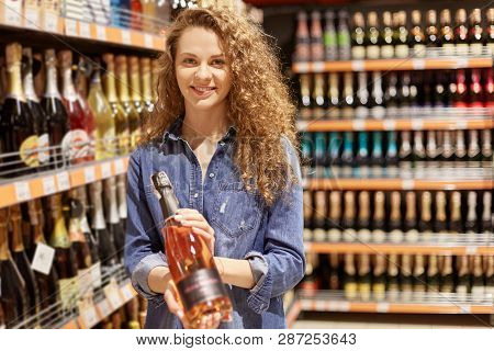 Charming Young Woman With Brown Curly Hair , In Denim Clothes. Holds Bottle Of Alcoholic Drink, Stan