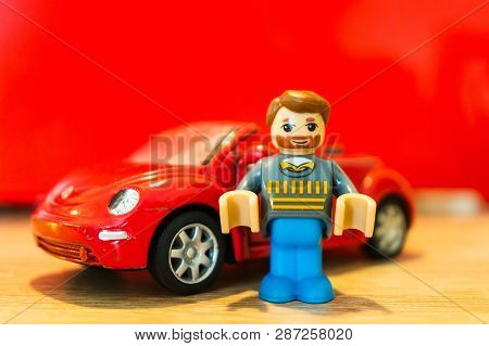 Poznan, Poland - February 15, 2019: Toy Man With Beard Figure Standing Next To His Parked Red Volksw