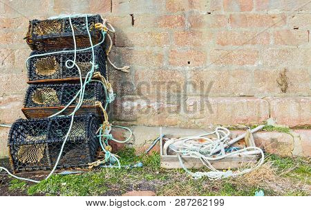 Lobster Pots Piled Against Stone Wall In Old Harbour
