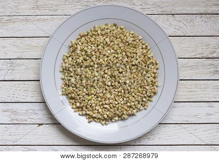 Sprouted Buckwheat On White Plate With Spoon On Brown Wooden Table. Top View. Organic Raw Hulled Gro