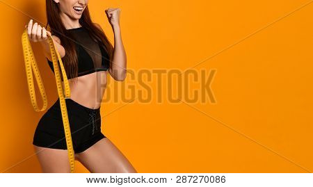 Athletic Slim Young Girl In Black Sportswear With A Measuring Tape In Her Hands Rejoices With A Gest