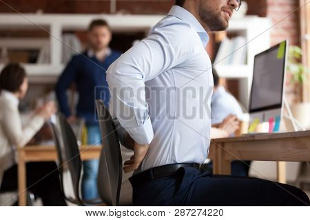Businessman Suffers From Lower Back Pain Sitting In Shared Office