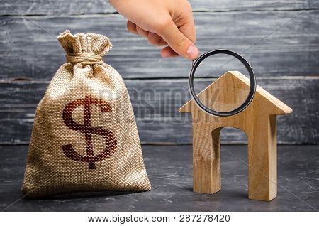 Magnifying Glass Is Looking At A Bag With Money And A House With A Large Doorway. Concept Of Real Es