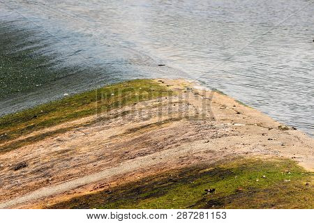 Partially dried man made waterfall during summer low water levels and drought season revealing concrete foundation covered with moss on warm sunny day poster