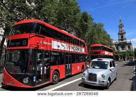 London, Uk - July 6, 2016: New Routemaster Bus And A Taxi Cab In London. The Hybrid Diesel-electric
