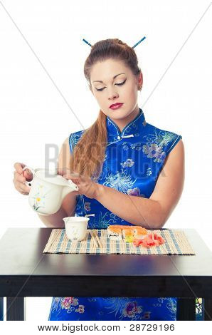 girl pouring tea and eating sushi
