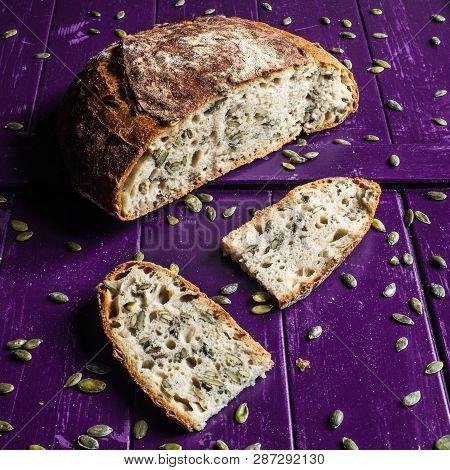 Pumpkin Seed Sourdough Bread On A Purple Wooden Board