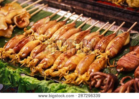 Traditional Asian Thai Street Food And Fast Food, Delicious Grilled Squid Calamari Skewers In Food M
