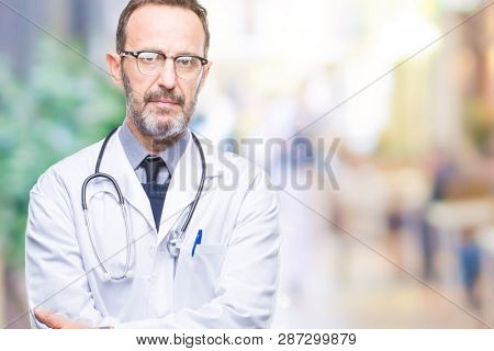 Middle age senior hoary doctor man wearing medical uniform isolated background with serious expression on face. Simple and natural looking at the camera.