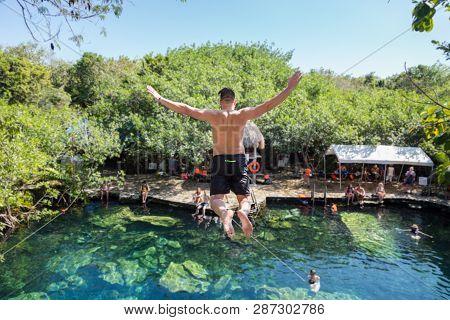 Man Jumps Off A Cliff Into The Cristalino Cenote In Mexico.