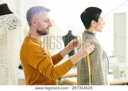 Mature professional tailor taking measures of jacket back while working with his client in tailoring shop