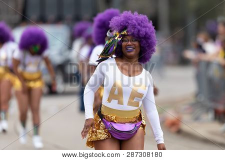 New Orleans, Louisiana, USA - February 23, 2019: Mardi Gras Parade, Alter Egos Steppers, African american dancer, smiling , wearing a purple wig, dancing during the parade