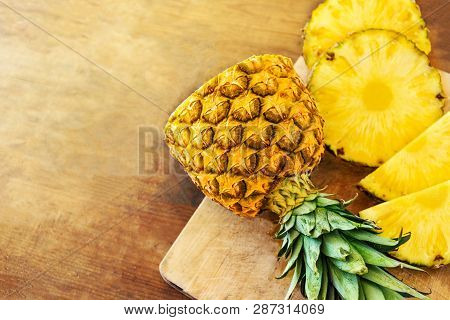 Pineapple On Wood Texture Background. Whole And Sliced Tropical Pineapple On Wooden Cutting Board  W