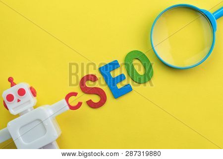 Seo Search Engine Optimization Concept With Vintage Robot With Magnifying Glass, Alphabet Abbreviati