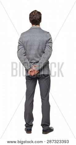 Back view of Business man looks.  Rear view people collection.  backside view of person. Isolated over white background. A young businessman in a gray suit stands with his arms folded behind his back