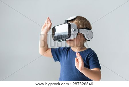 Portrait of happy boy in a virtual reality headset. Attractive kid using vr goggles at home. Entertainment technology and generation Z concept.
