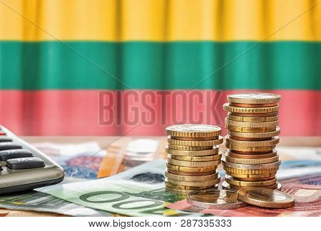 Euro Banknotes And Coins In Front Of The National Flag Of Lithuania