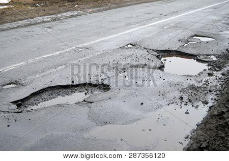 Poor condition of the road surface. Winter season. Hole in the asphalt, risk of movement by car, bad asphalt, dangerous road, potholes in asphalt. February 4, 2019. Kiev,Ukraine