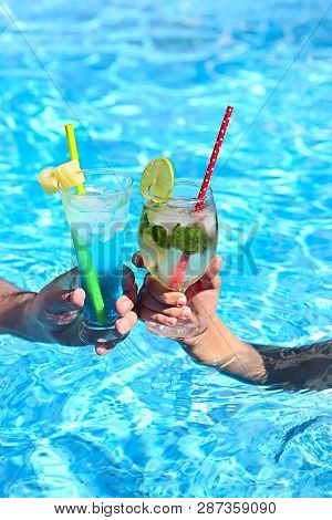 Young Couple With Glasses Of Alcohol Cocktails Mojito And  Blue Lagoon In The Swimming Pool