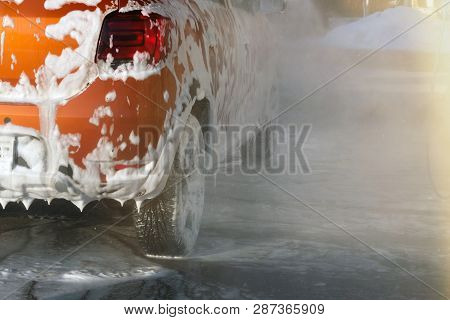 Car is cleaning with soap suds at self-service car wash. White lather on auto. Water splashes around car and soapy water runs down. poster