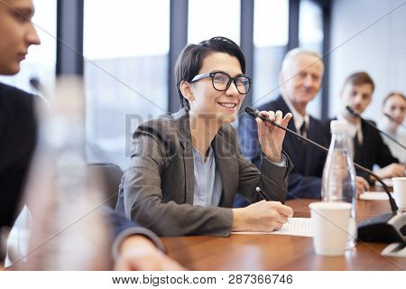 Portrait Of Smiling Businesswoman Speaking To Microphone During Press Conference Or Training Seminar