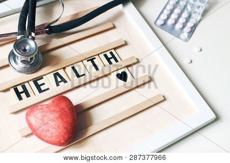 Closeup Of Red Heart Stone, Stethoscope, Wooden Letter Board And Pills On White Table Background. He