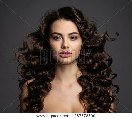 Beautiful young woman with long curly brown hair and  smoky eye makeup. Sexy and gorgeous brunette girl  with a wavy hairstyle. Portrait of an attractive female. Fashion model.
