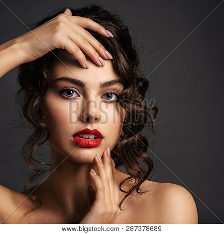 Beautiful young woman with long curly brown hair and  smoky eye makeup. Sexy and gorgeous brunette girl  with a stylish hairstyle. Portrait of an attractive female. Fashion model.