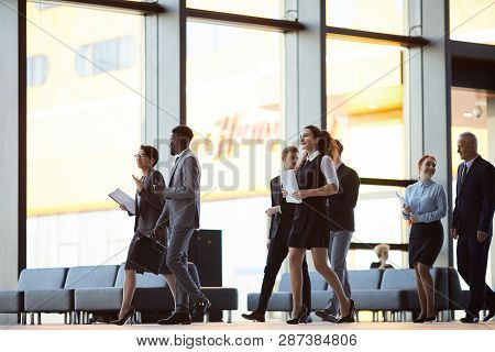 Full Length Portrait Of Business People Walking Across Office Hall Of Lobby, Copy Space