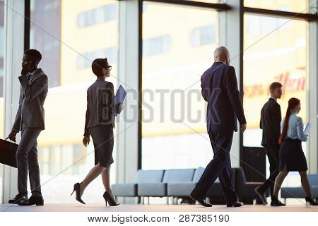 Back View Of Business People Walking In Office Hall Or Lobby, Copy Space