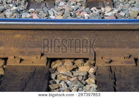 Railroad Track Closeup With Iron Plate, Pins, Ties, Stone Ballast