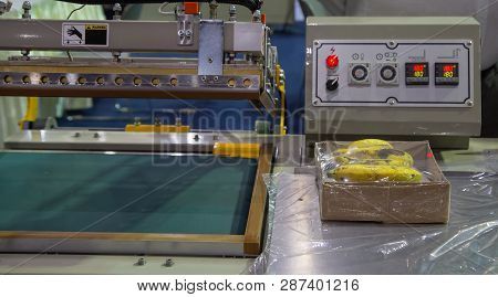 Industrial Plastic Shrink Wrapping Machine Packing A Carton Of Banana