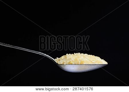 Raw Rice Poured Into A Silver Spoon. Side View On A Black Background. Minimalism And Space For Text.