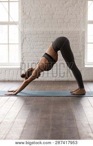 Young Woman Practicing Yoga, Downward Facing Dog, Adho Mukha Svanasana