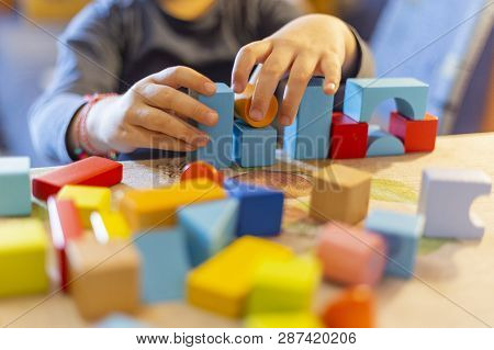 A Child Plays With Colored Wooden Blocks At Home.kid Plays And Builds Buildings And Towers With Wood