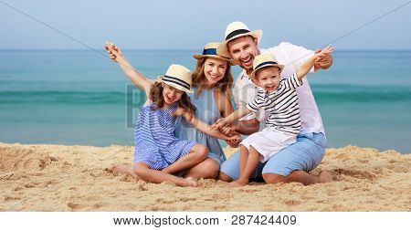 Happy Family Father, Mother And Children On The Beach At Sea