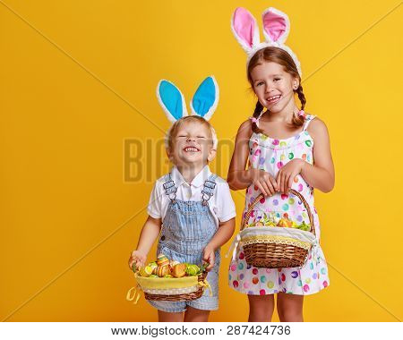 Funny Happy Child Boy And Girl  With Easter Eggs And Bunny Ears On Yellow Background