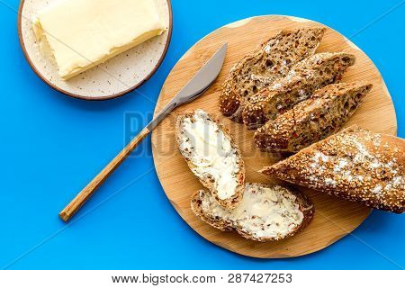 Bread On Cutting Board With Butter On Plate, Slice Of Bread With Butter On Blue Background Top View