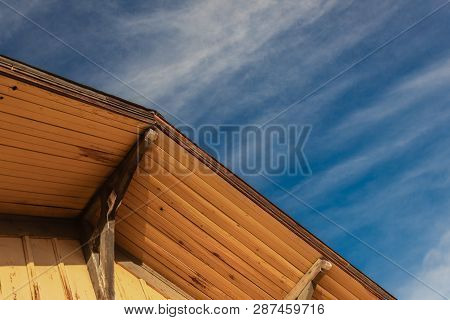 Old Building Construction, Peak Corbels And Eaves, Board And Batten, Blue Sky, Horizontal Aspect