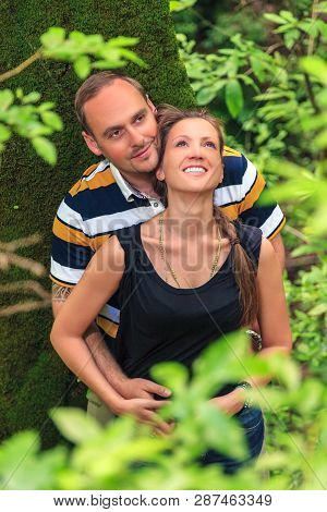 Sochi, Russia - May 30, 2014: Young Happy Loving Caucasian Couple Embracing And Dreaming Outdoor In