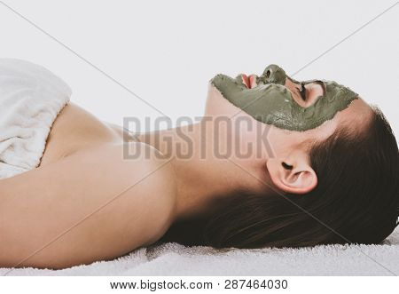 Side view of lying woman with green facial clay mask, white background.