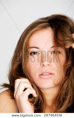 Redhead woman with fleckles on white background. Sensual lady.
