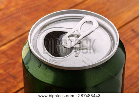 Can with drink view from the top. Green open soda aluminum can. Shiny metalic beer container close up
