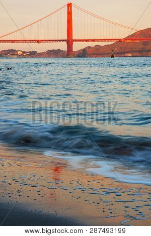 Golden Gate Bridge In Warm Red Color Of Aurora And It's Reflection On Sand