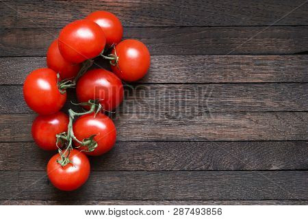 Tomatoes On Dark Wooden Table With Copy Space