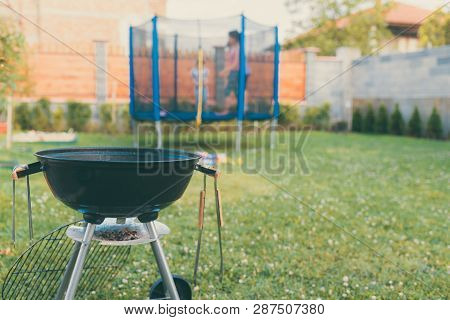 Kettle Charcoal Bbq Barbecue Grill In Garden Or Backyard. Blurred Outdoor Trampoline In The Backgrou