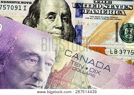 A Purple Canadian Ten Dollar Bill Paired With A Blue American One Hundred Dollar Bill