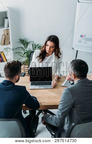 Advisor Showing To Investors Laptop With Blank Screen At Workplace