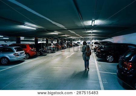 Karlsruhe, Germany - Oct 29, 2017: Rear View Of German Woman Walking Toward Car In New Underground P
